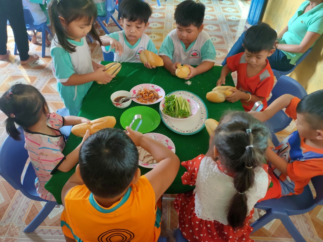 Các bé chăm chú cản thận làm bánh mì theo các bước cô đã hướng dẫn