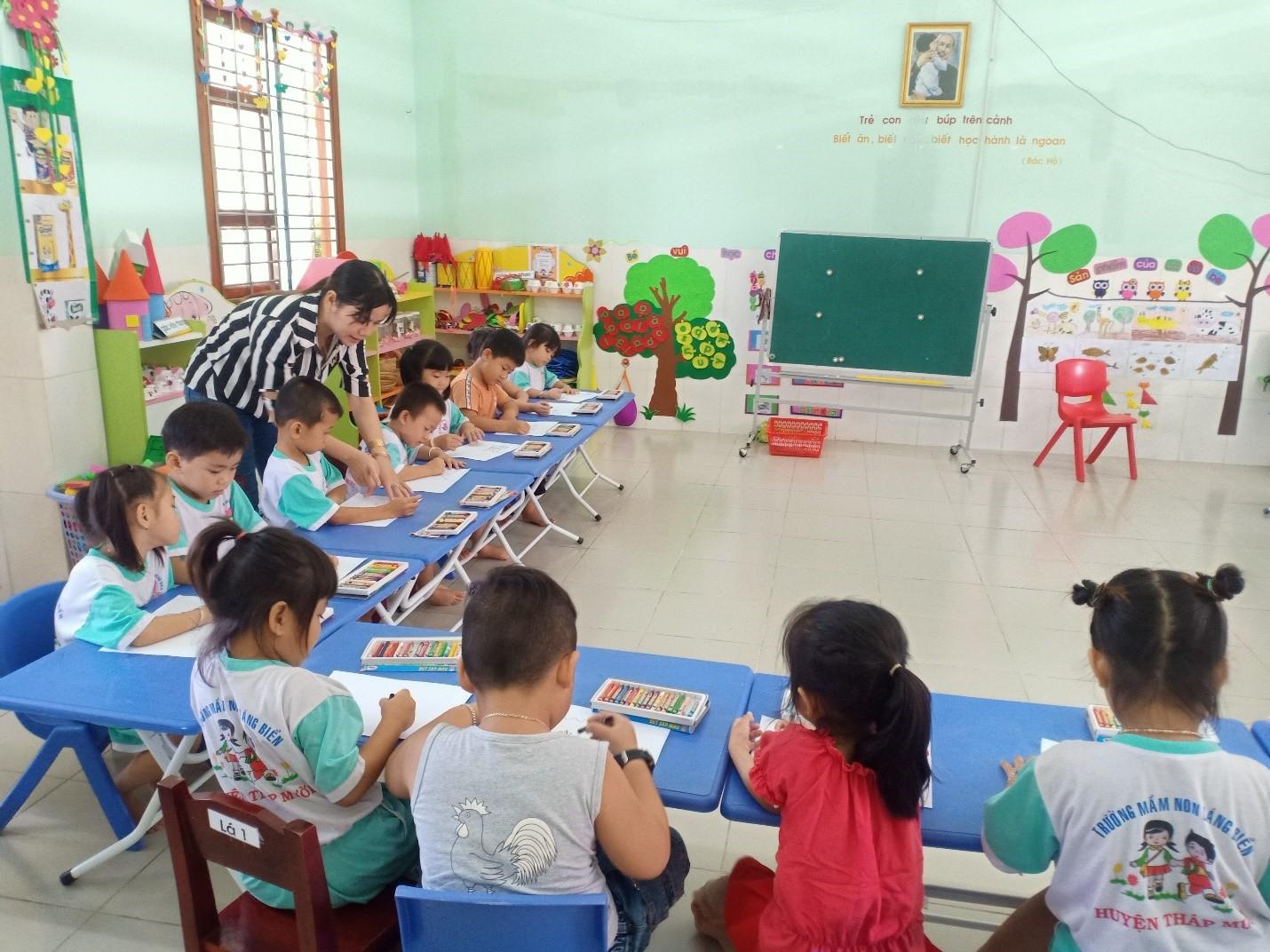 Cô giáo quan sát và giúp đỡ những trẻ còn yếu